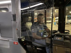 Bus driver sits behind operator safety shield