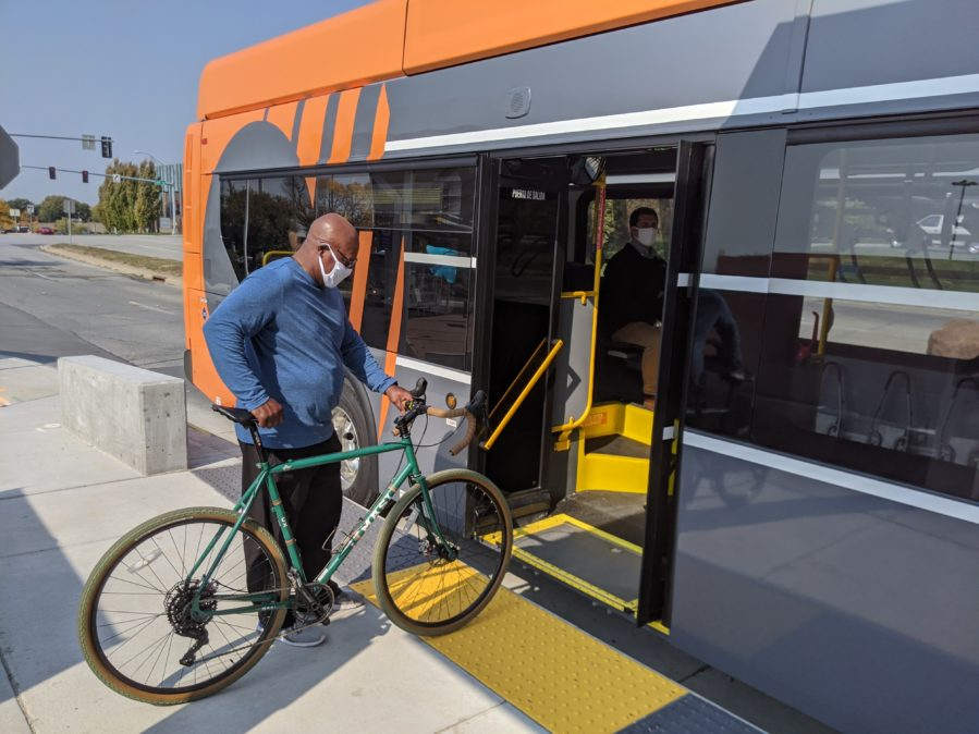 Bus rider bringing bicycle onboard an ORBT bus at the rear doors